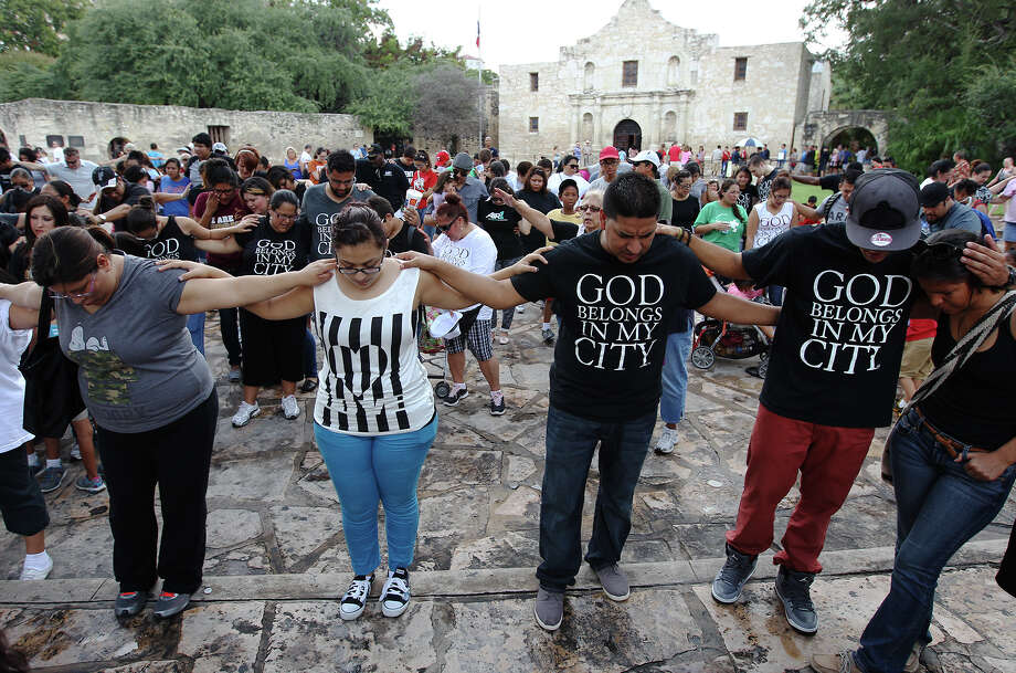 "Worshippers pray while attending the third annual God Belongs in my City walk on Saturday, Sept. 28, 2013. The event which started at Milam Park and finished at Alamo Plaza concluded with songs and prayers. The gathering is a ""worldwide calling for all Christians to pray for spiritual awakening"" according to pastor Sammy Lopez of Mighty Fortress Christian Fellowship who led the event. Photo: Kin Man Hui, San Antonio Express-News / ©2013 San Antonio Express-News"