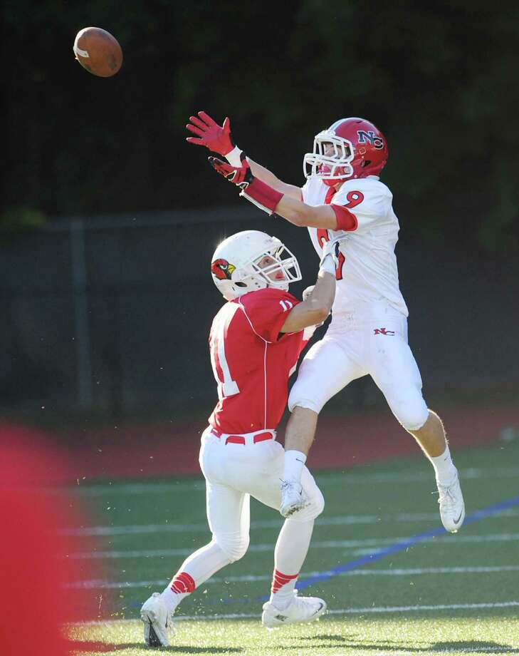 New Canaan receiver Cole Turpin (# 9), right, makes a reception as Ryan Pasquali (# 11) of Greenwich defends during the high school football game between Greenwich High School and New Canaan High School at Greenwich, Saturday, Sept. 28, 2013. Photo: Bob Luckey / Greenwich Time
