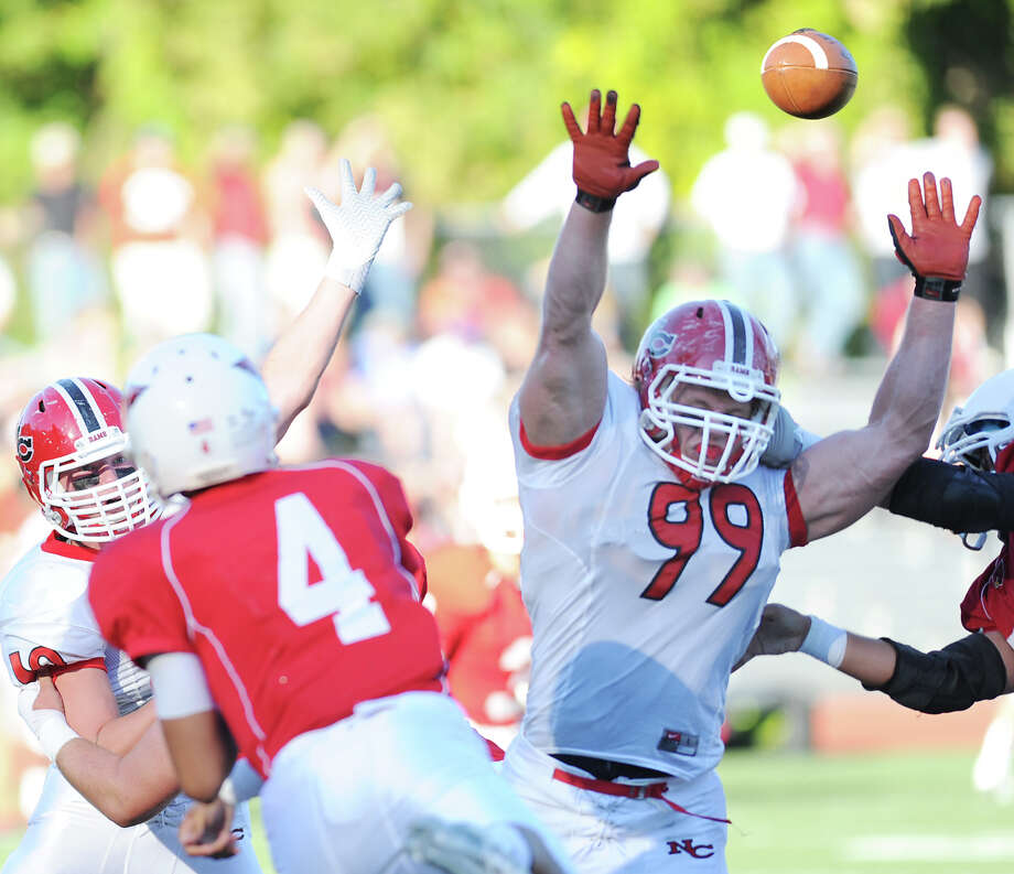 New Canaan's Connor Buck (# 99) gets both arms up as Greenwich quarterback Jose Melo (# 4) attempts a second quarter pass during the high school football game between Greenwich High School and New Canaan High School at Greenwich, Saturday, Sept. 28, 2013. Photo: Bob Luckey / Greenwich Time