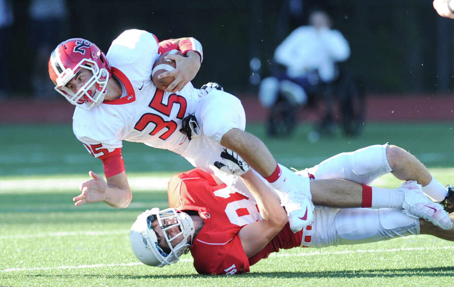Running back Seth Neeleman (# 35) of New Canaan is tackled by Stephen Lewis (# 81) of Greenwich, at bottom, during the high school football game between Greenwich High School and New Canaan High School at Greenwich, Saturday, Sept. 28, 2013. Photo: Bob Luckey / Greenwich Time