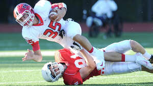 Running back Seth Neeleman (# 35) of New Canaan is tackled by Stephen Lewis (# 81) of Greenwich, at bottom, during the high school football game between Greenwich High School and New Canaan High School at Greenwich, Saturday, Sept. 28, 2013.