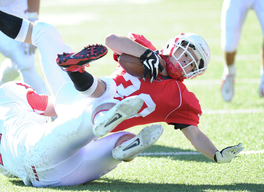 Greenwich running back Thomas Rappa, right, gets tackled by a New Canaan defender during the high school football game between Greenwich High School and New Canaan High School at Greenwich, Saturday, Sept. 28, 2013. Photo: Bob Luckey / Greenwich Time