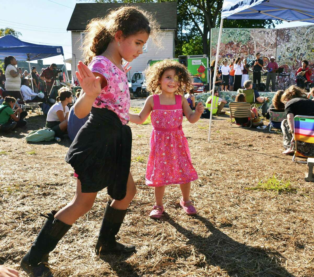 Sisters, Lina,7, left, and Lara Markovitch, 4, of Brunswick dance to the music of Nawal during the Third Annual Celebration of Art and Food from Seed to Table, Story Harvest, at Freedom Square Saturday Sept. 28, 2013, in Troy, NY. (John Carl D'Annibale / Times Union)