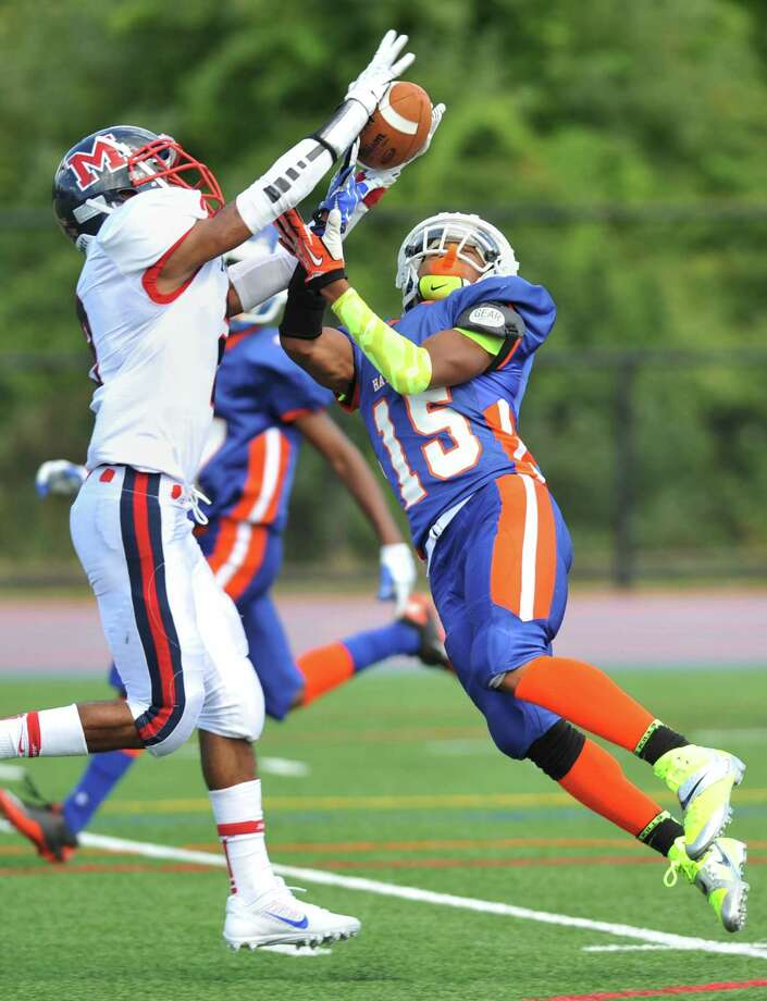 Brien McMahon defender Malik Whittaker, left, rises up to grab an interception from Danbury receiver Tysheen McCrea infrom the FCIAC high school football game between Danbury and Brien McMahon at Danbury High School in Danbury, Conn. on Tuesday, Sept. 24, 2013.  Brien McMahon defeated Danbury, 21-7. Photo: Tyler Sizemore / The News-Times