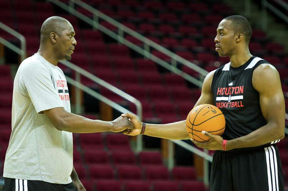 From one great center to another, the Dream greets Superman. Hakeem Olajuwon, left, was on hand for the first day of Rockets training camp, which also was the first day of the Dwight Howard era at Toyota Center. Photo: Smiley N. Pool, Staff / © 2013  Houston Chronicle