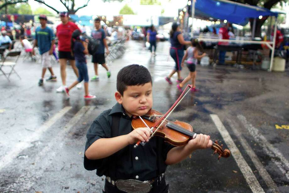 Zeshua Longoria, 7, warms up before performing with his the mariachi group, Mariachi Serenata Juvenil at the St. Joseph Catholic Church Fall Festival near downtown Saturday, Sept. 28, 2013, in Houston. Photo: Johnny Hanson, Houston Chronicle / Houston Chronicle
