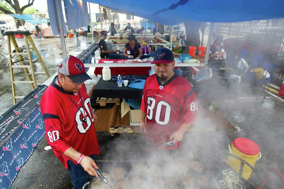 Arnold Rangel, left, and Julian Tijerina cook hamburgers in the Texans Burger booth at the St. Joseph Catholic Church Fall Festival near downtown Saturday, Sept. 28, 2013, in Houston. Photo: Johnny Hanson, Houston Chronicle / Houston Chronicle