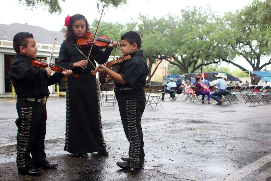 Zayden Longoria, left, his brother, Zeshua Longoria, 7, and Angela Salazar, 13, warm up before performing with their the mariachi group, Mariachi Serenata Juvenil, at the St. Joseph Catholic Church Fall Festival near downtown Saturday, Sept. 28, 2013, in Houston. Photo: Johnny Hanson, Houston Chronicle / Houston Chronicle