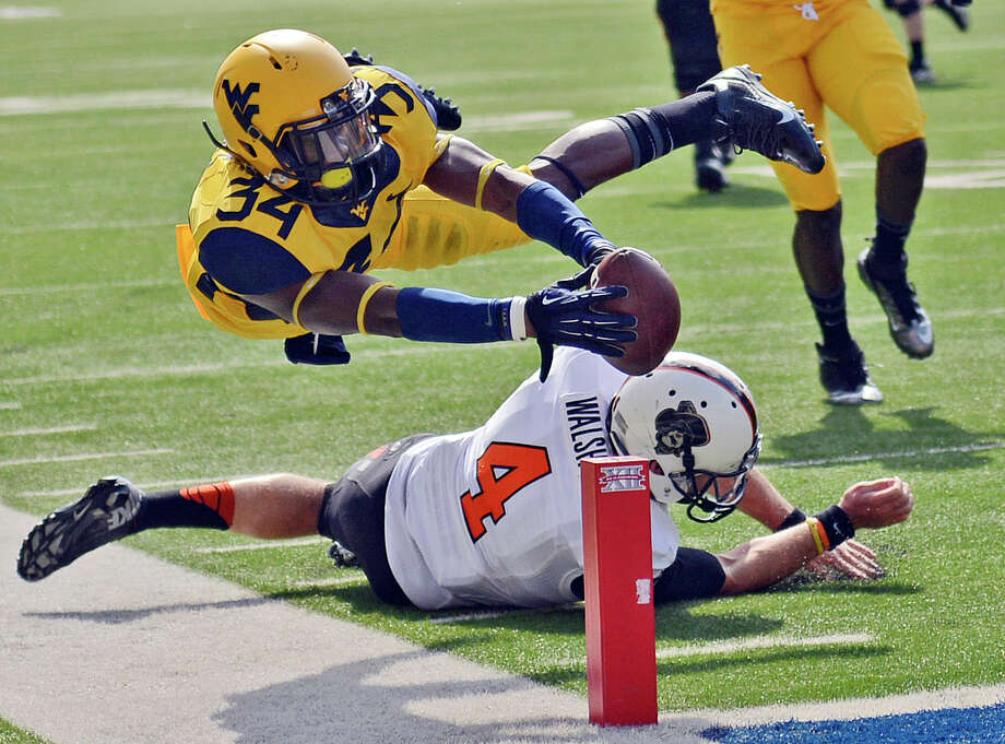 West Virginia' Ishmael Banks soars past Oklahoma State quarterback J.W. Walsh to score on a 58-yard interception return Saturday. Photo: Tyler Evert, FRE / FR170609