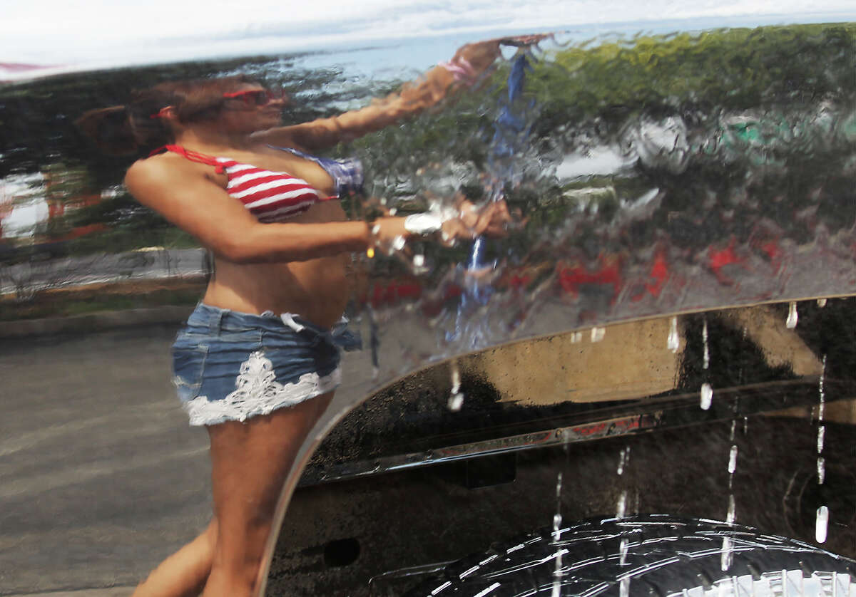 """Hooters employee Gracie Rivera is reflected off the surface of a truck as she rinses off the soap from the vehicle during a charity car wash for donations to help two Selma police officers, Tiffany Kierum and Jesus Balderamas, who both were shot and wounded while responding to a family violence call earlier in the month. The Hooters restaurant located in Selma held the car wash on Saturday, Sept. 28, 2013. Manager Joe Cossio said Kierum worked at Hooter's for about six years before she became a police officer. """"I couldn't ask fo an employer like she was. She was great,"""" Cossio said. The donations from an earlier bake sale and the car wash will be matched by the corporation according to Cossio. Approaching the afternoon, over 20 vehicles had already been washed and dried at the charity event."""
