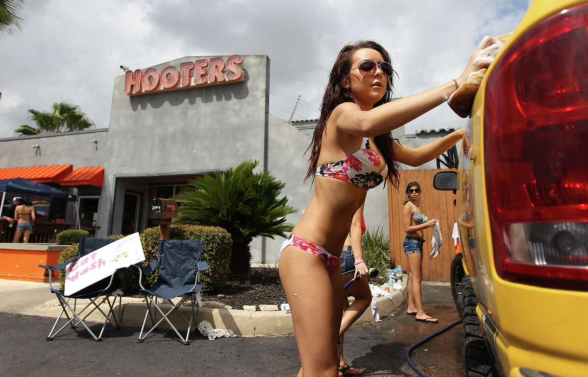 """Hooters employee Ariel Davis applies soap to a vehicle during a charity car wash for donations to help two Selma police officers, Tiffany Kierum and Jesus Balderamas, who both were shot and wounded while responding to a family violence call earlier in the month. The Hooters restaurant located in Selma held the car wash on Saturday, Sept. 28, 2013. Manager Joe Cossio said Kierum worked at Hooter's for about six years before she became a police officer. """"I couldn't ask fo an employer like she was. She was great,"""" Cossio said. The donations from an earlier bake sale and the car wash will be matched by the corporation according to Cossio. Approaching the afternoon, over 20 vehicles had already been washed and dried at the charity event."""