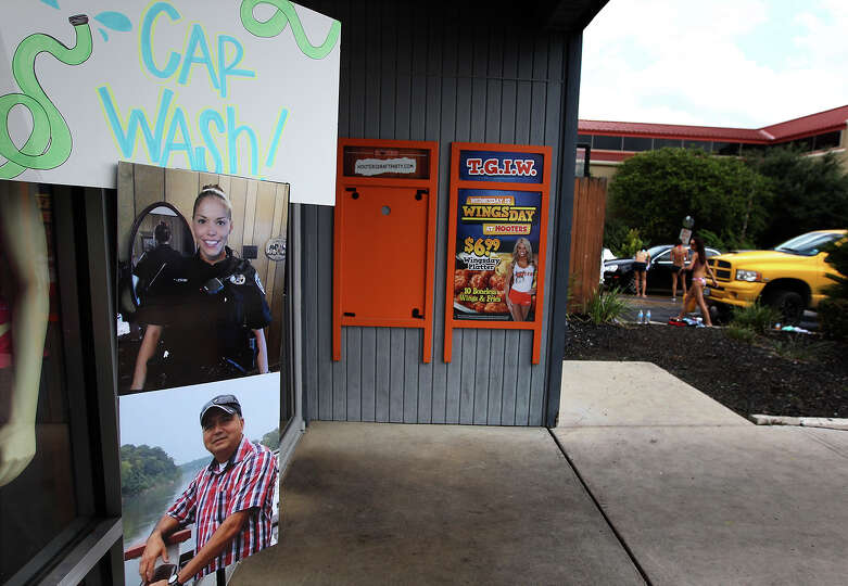 Hooters employees hold a charity car wash for donations to help two