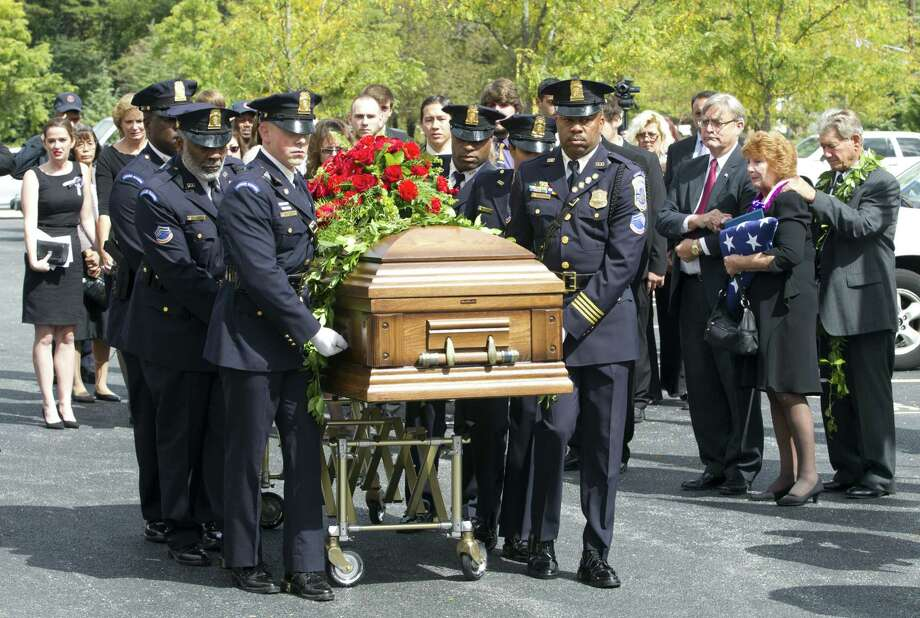 "Police officers carry the coffin of Richard ""Mike"" Ridgell, 52, after his funeral service in Severn, Md. Ridgell was known as a cheerful person who follwed security rules to the letter. Photo: Luis Magana / Associated Press"