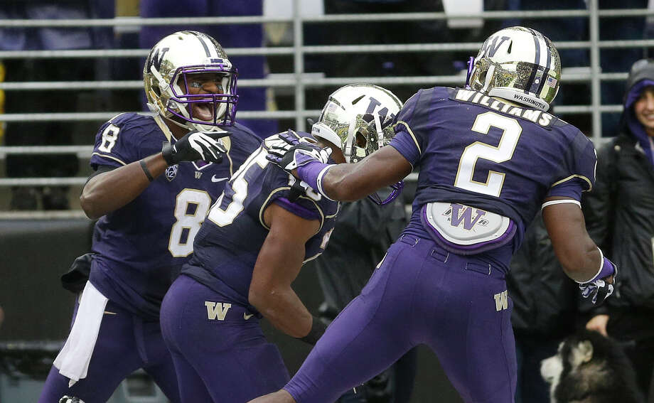 Washington wide receiver Kevin Smith (8), left, celebrates with Bishop Sankey, center, and Kasen Williams (2) after Smith scored a touchdown against Arizona during the first half Saturday. Photo: AP