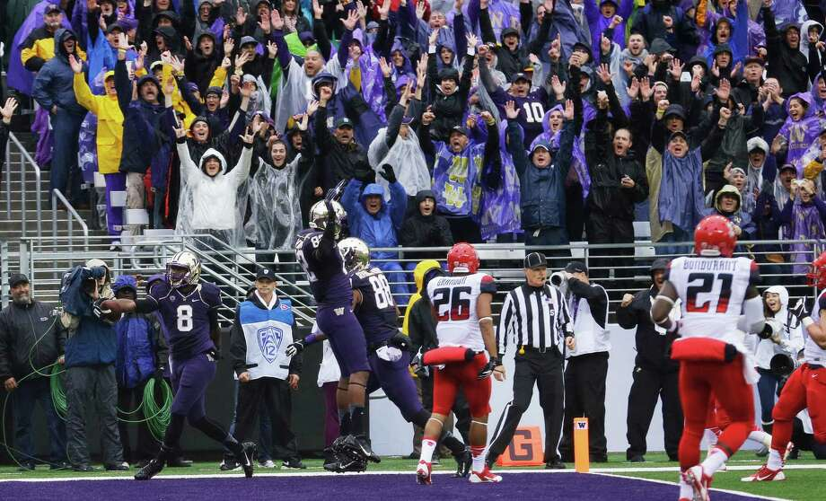 Fans celebrate as Washington wide receiver Kevin Smith (8), left, scored a touchdown in the first half against Arizona on Saturday.  Photo: AP