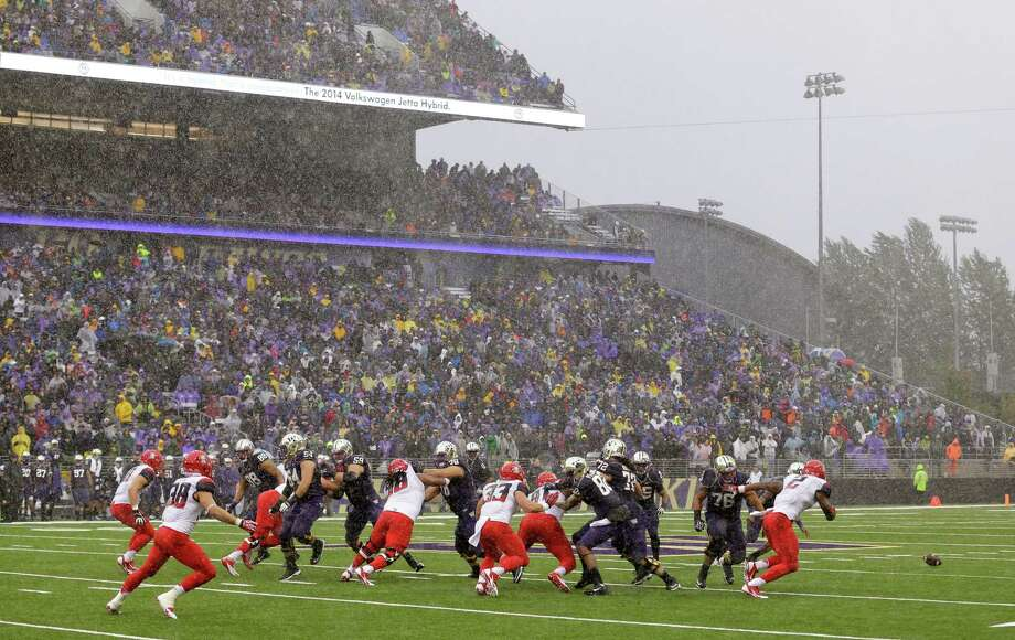 Heavy rain falls during a fumble on a Washington possession against Arizona in the first half on Saturday.  Photo: AP
