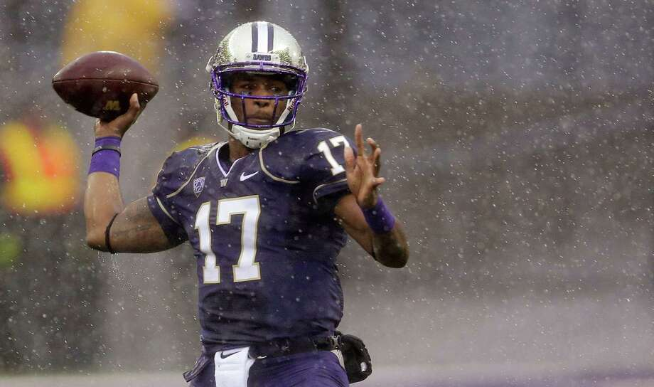 Washington quarterback Keith Price passes in the rain during the first half against Arizona on Saturday. . Photo: AP
