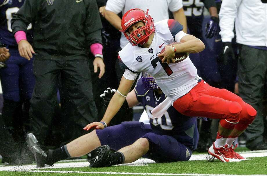 Arizona quarterback B.J. Denker (7) is tackled by Washington's Evan Hudson, left, in the first half on Saturday. Photo: AP