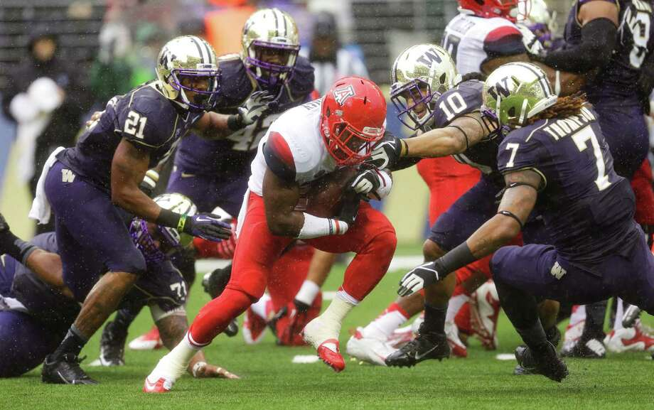 Arizona running back Ka'Deem Carey, center, rushes against Washington's John Timu (10) and Shaq Thompson in the first half. Photo: AP