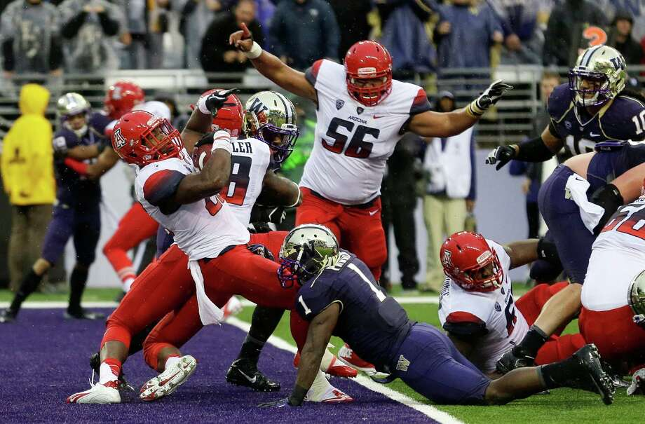 Arizona's Ka'Deem Carey, left, falls in backwards for a touchdown as Washington's Sean Parker (1) tries the tackle and Arizona's Steven Gurrola (56) raises his hands in celebration during the first half. Photo: AP