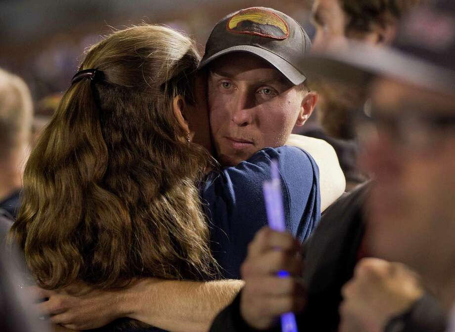 FILE - In this July 2, 2013 file photo, firefighter Brendan McDonough embraces a mourner near the end of a candlelight vigil in Prescott, Ariz. McDonough was the sole survivor of the 20-man Granite Mountain Hotshot Crew after an out-of-control blaze killed the 19 near Yarnell, Ariz. Investigators are set to release a report Saturday, Sept. 28, 2013, on the deaths of the 19 elite firefighters who became trapped by flames in a brush-choked canyon north of Phoenix.(AP Photo/Julie Jacobson, File) ORG XMIT: AZMY202 Photo: Julie Jacobsen / AP