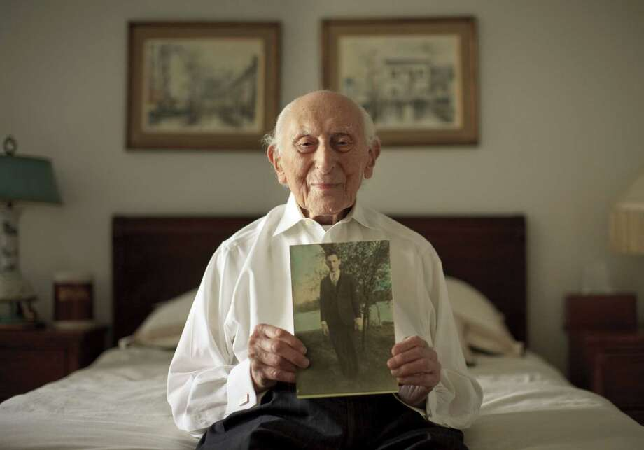 Harry Rosen, 103, holds a photo of himself as a young man in the 1920s. Rosen, who emigrated to the United States from Russia when he was 11, lives alone, dining out at expensive restaurants. Photo: Dave Sanders / New York Times