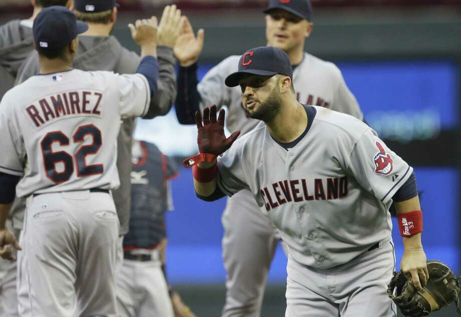 The Indians' Nick Swisher (right) celebrates with his teammates after Cleveland won its ninth straight. Photo: Jim Mone / Associated Press