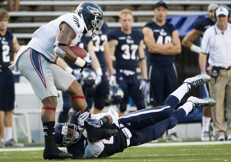 Florida Atlantic wide receiver Daniel McKinney (8) is tripped up by Rice safety Malcolm Hill (2).