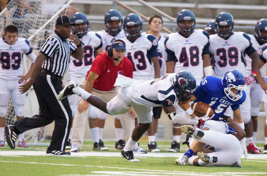Cy-Creek wide receiver Matt Shoffner (15) is taken down by Cy-Spring  outside linebackers Lawrence Ghansah (left) and Andrew Perkins during the first half of a high school football game at Pridgeon stadium on Saturday, Sept. 28, 2013, in Houston. Photo: J. Patric Schneider, For The Chronicle / © 2013 Houston Chronicle