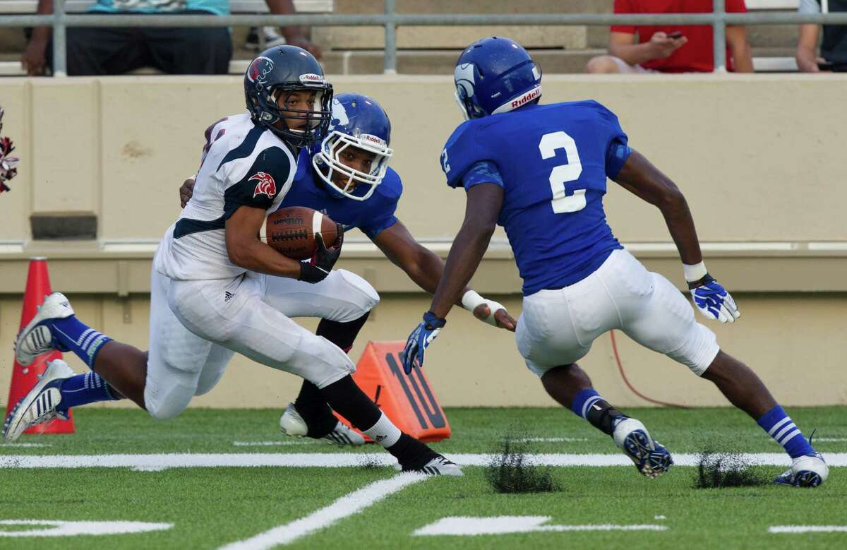 Cy-Spring wide receiver Michael Ewing (11) runs past Cy-Creek defensive back Jay Beck (2) and linebacker Jacoby Brooks during the first half of a high school football game against Cy-Creek at Pridgeon stadium on Saturday, Sept. 28, 2013, in Houston.