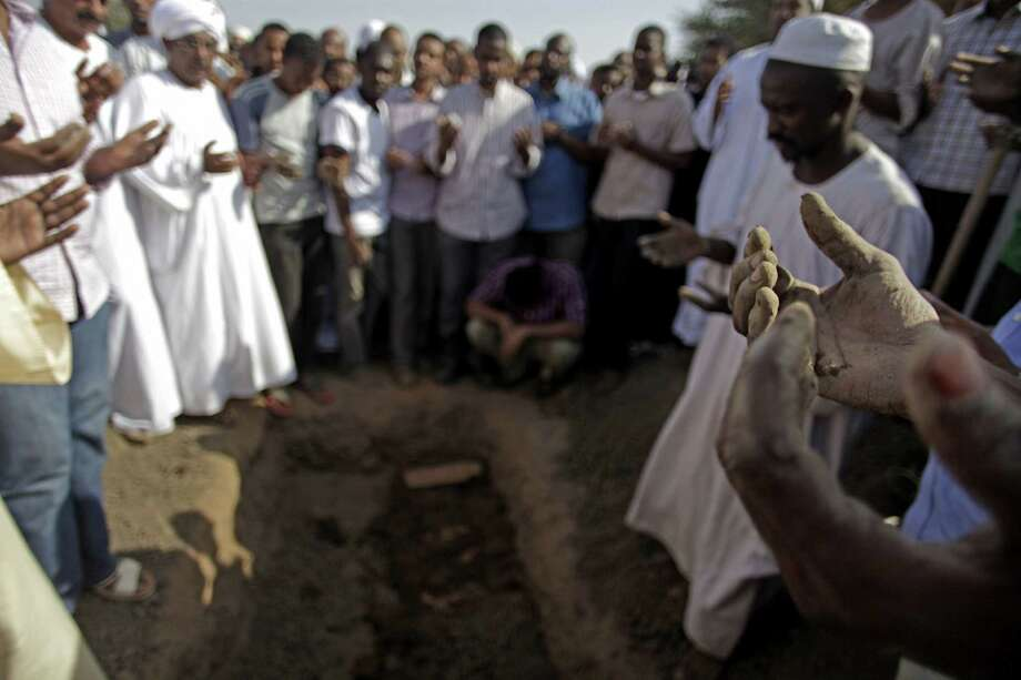 Sudanese men pray over the body of Salah Sanhory, 26, who was killed on Friday by security forces, during his funeral Saturday in Khartoum, Sudan. Photo: Khalil Hamra / Associated Press