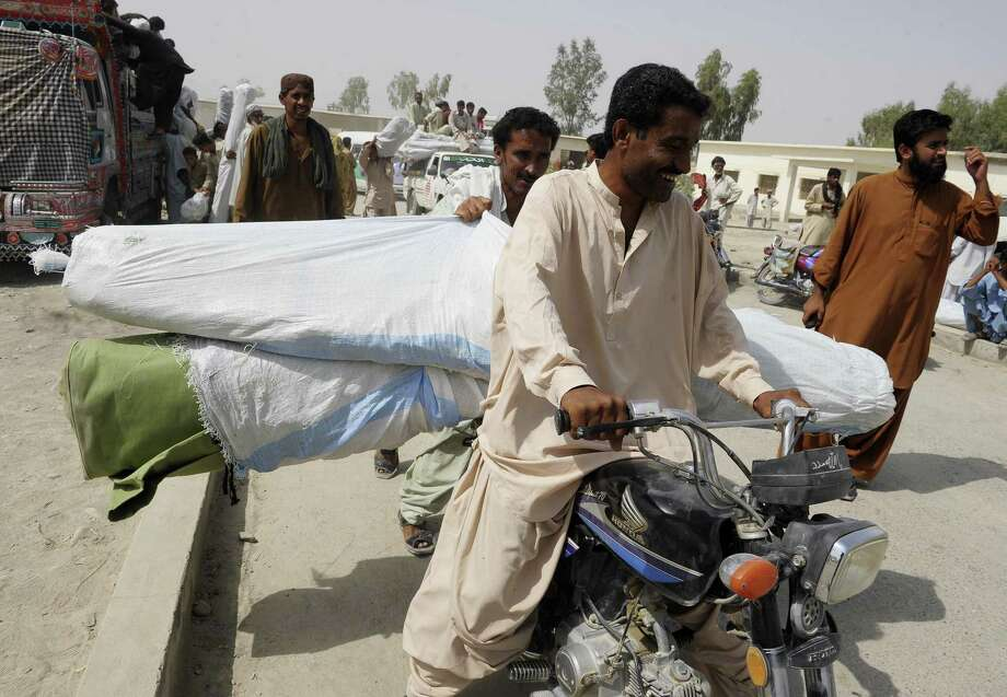 Pakistani earthquake survivors carry tents from a distribution point in the Awaran district after a 6.8-magnitude earthquake. The region was devastated by a tremor last week that killed more than 300. Photo: Banaras Khan / Getty Images