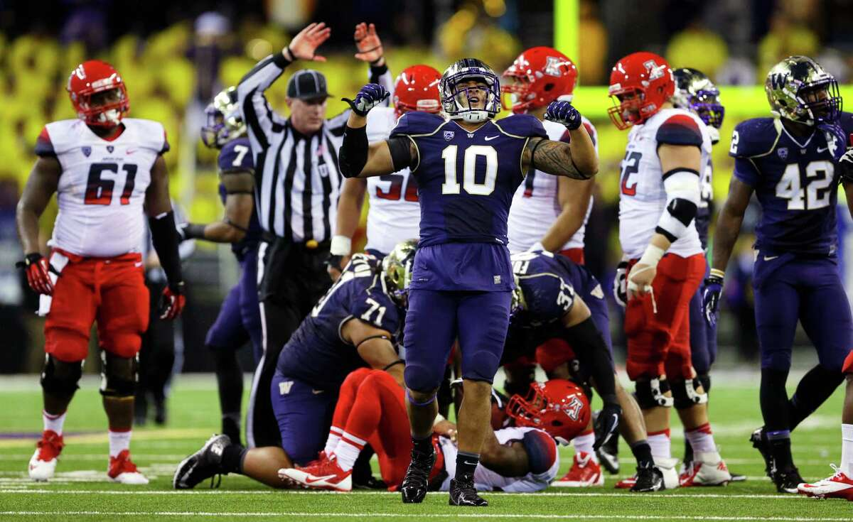 Washington linebacker John Timu (10) celebrates a defensive play against Arizona late in the fourth quarter Saturday. UW won 31-13..
