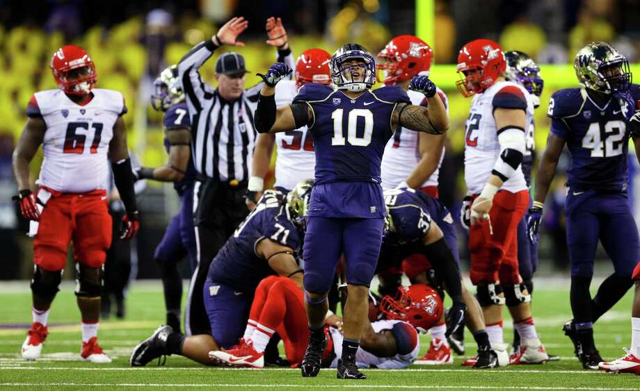 Washington linebacker John Timu (10) celebrates a defensive play against Arizona late in the fourth quarter Saturday. UW won 31-13.. Photo: AP