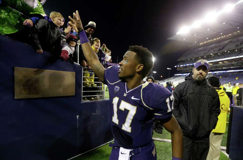 Washington quarterback Keith Price (17) tosses a towel to a fan as he leaves through the tunnel after Washington defeated Arizona 31-13. Photo: AP