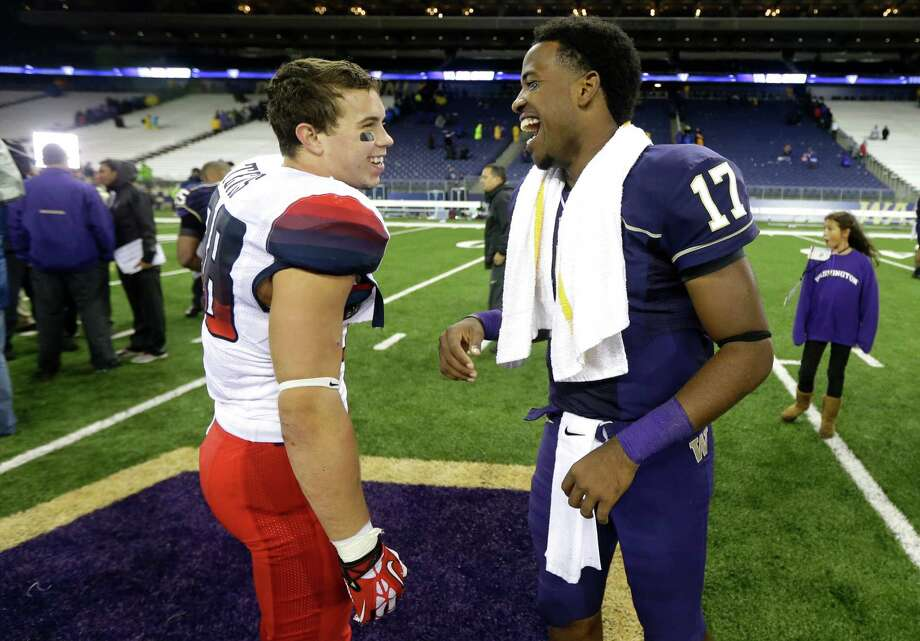 Washington quarterback Keith Price (17) smiles as he talks with Arizona's Jared Tevis, left, after Washington defeated Arizona 31-13. Photo: AP