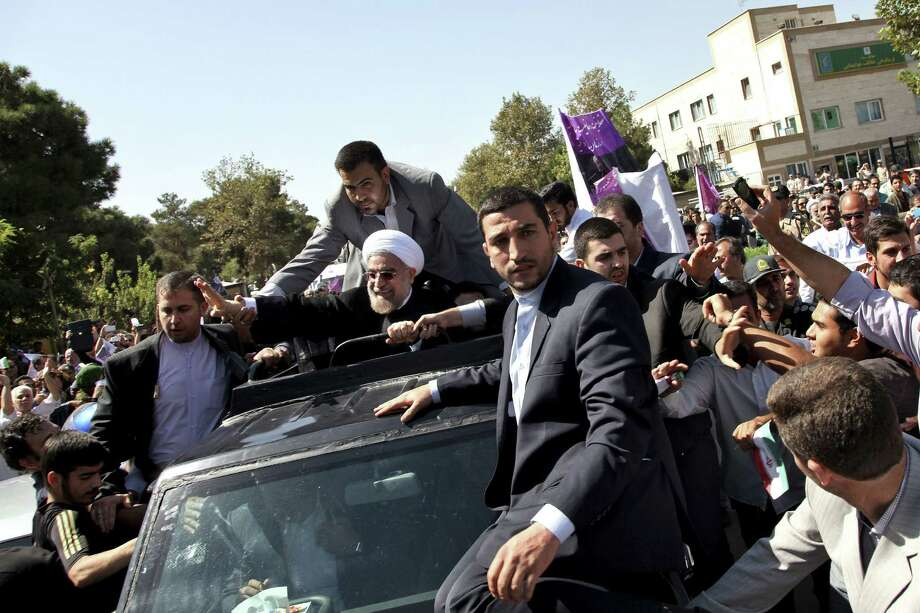 Iranian President Hassan Rouhani (center) waves to supporters upon his arrival from the U.S. near the Mehrabad airport in Tehran on Saturday. Iranians from across the political spectrum both decried and hailed the telephone conversation between President Barack Obama and Rouhani. Photo: Ebrahim Noroozi / Associated Press
