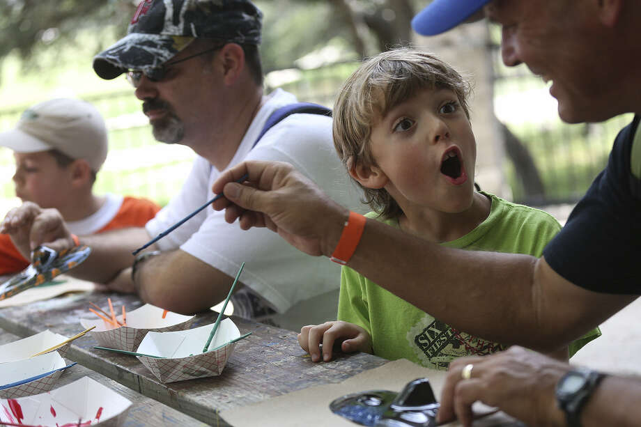 Dylan Fletcher, 7, and his dad, Gary Fletcher (right), paint superhero masks Saturday at New Scout Superhero Academy at McGimsey Scout Park. Photo: Lisa Krantz / San Antonio Express-News