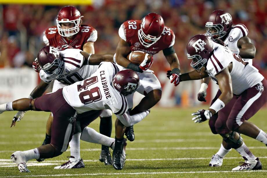 Jonathan Williams #32 of the Razorbacks is tackled by Darian Claiborne #48 of the Aggies. Photo: Wesley Hitt, Getty Images