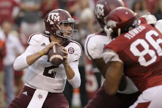 Texas A&M quarterback Johnny Manziel (2) looks for a receiver as he prepares to pass over Arkansas defensive end Trey Flowers (86). Photo: Danny Johnston, Associated Press