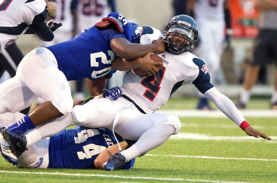 Cypress Creek linebacker John Head (20) takes down Cypress Springs quarterback Troy Brown (4) in the first half of Saturday's District 17-5A game. Photo: J. Patric Schneider, Freelance / © 2013 Houston Chronicle