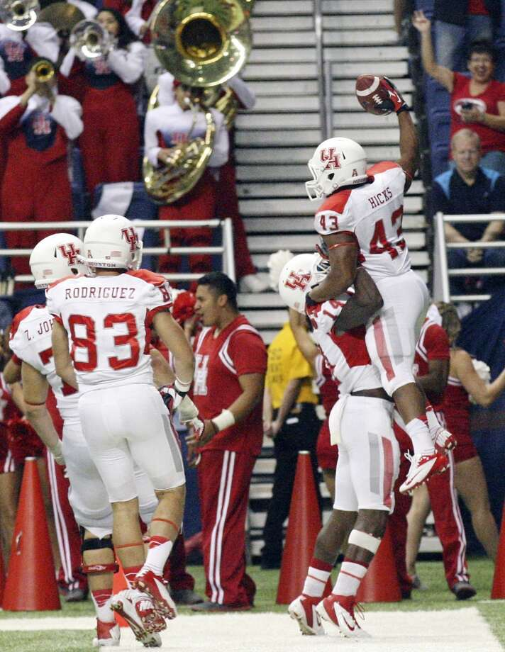 University of Houston's Zach Johnson (from left), and Andrew Rodriguez watch as teammates Aaron Johnson and Justin Hicks celebrate after Hicks scored a touchdown against UTSA during second half action Saturday Sept. 28, 2013 at the Alamodome. The University of Houston won 59-28. Photo: San Antonio Express-News