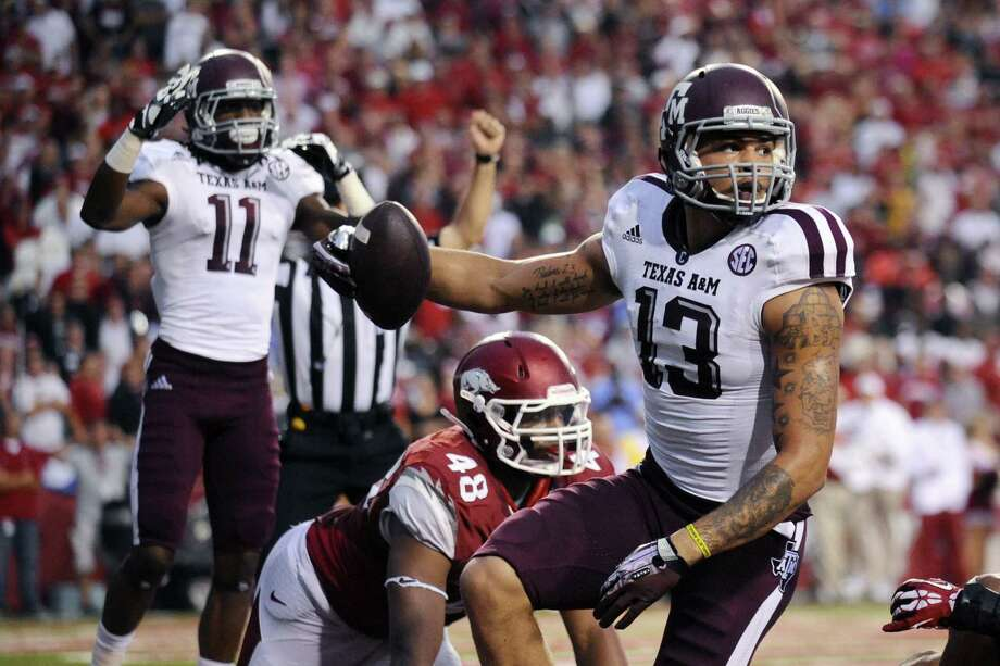 A&M's Mike Evans (13) and Derel Walker (11) celebrate Evans' 7-yard TD catch in the second quarter over Arkansas' Deatrich Wise Jr. Evans also added a 9-yard TD catch in the first. Photo: Beth Hall / Associated Press
