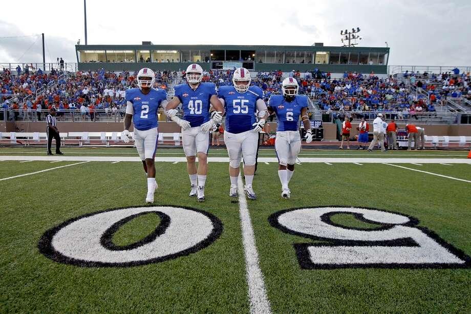 Darian Lazard #2, Garrett Dolan #40, TC Jones #55 and Ja'Halen Norris walk toward the coin flip. Photo: Thomas B. Shea, Houston Chronicle