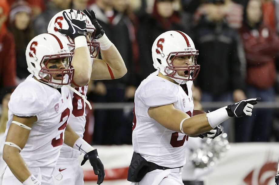 Devon Cajuste (right) reacts after the first of his two touchdowns, a 57-yard pass from Kevin Hogan in the first quarter. Photo: Elaine Thompson, Associated Press