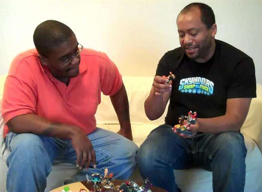 "Chris Wilson, a producer with Activision, explains ""Skylanders Swap Force"" to M4d Ski11z at Willie Jefferson Jr.'s house in Houston, Texas. Photo: Willie Jefferson Jr."