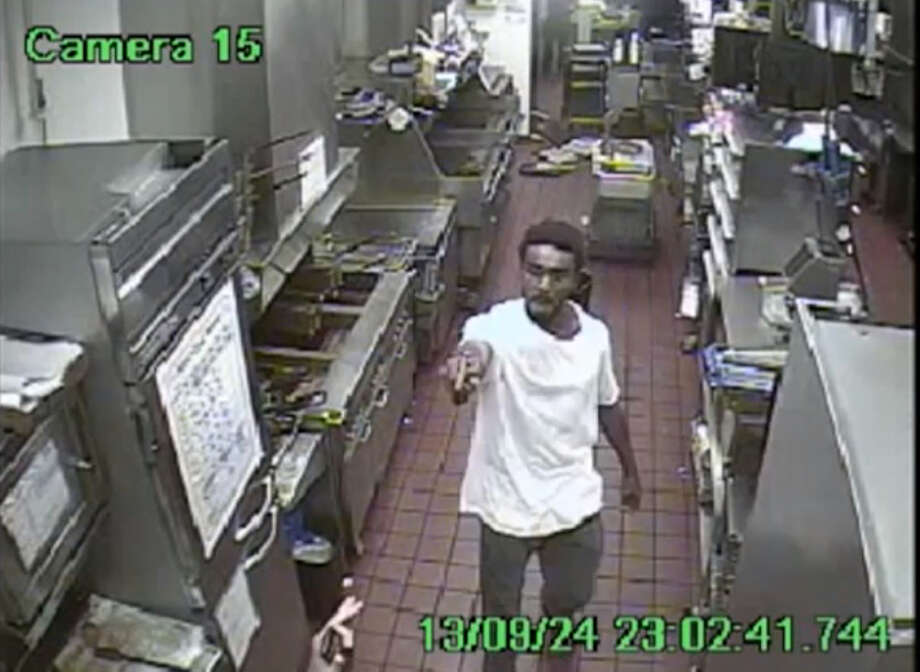 In this image made from surveillance video taken Tuesday, Sept. 24, 2013, and provided by the Fort Worth Police Department, would-be robber Jestin Anthony Joseph points a gun at a person inside a McDonald's in Fort Worth, Texas. Witnesses said Joseph threatened a customer at the counter and tried to fire the gun, but it jammed. Joseph was arrested and remained jailed Friday, Sept. 27, 2013, on $500,000 bond. Photo: AP