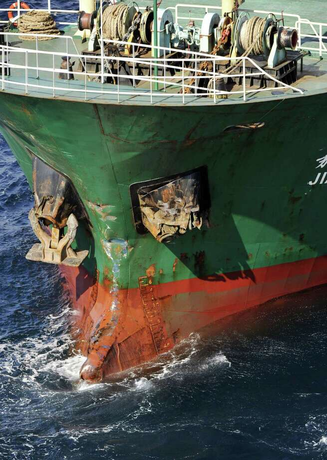 In this aerial photo, the Sierra Leone-registered freighter Jia Hui sails off Izu Oshima, Japan, following a collision with a Japanese freighter, Friday, Sept. 27, 2013. The ship crashed with Japanese ship Eifuku-maru No.18 early Friday. The Japanese ship was capsized as a result, missing crew members including the skipper and deputy skipper. The 12 Chinese and one Malay on the Jia Hui appear to be safe, but details are being confirmed. (AP Photo/Kyodo News)  Photo: AP