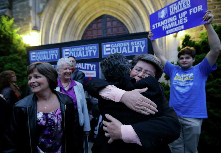 Cindy Meneghin, second from right, hugs her attorney Hayley Gorenberg during a rally at Garden State Equality in Montclair, N.J., hours after a Superior Court Judge ruled that New Jersey is unconstitutionally denying federal benefits to gay couples and must allow them to marry Friday, Sept. 27, 2013. Meneghin has been with her partner, Maureen Kilian, left, for 39 years. Judge Mary Jacobson ruled it legal for gay couples to marry in the state beginning Oct. 21, 2013. The ruling comes after a group of gay marriage supporters sued the state in July, days after the U.S. Supreme Court struck down key parts of a law that blocked the federal government from granting benefits to gay couples. Photo: AP