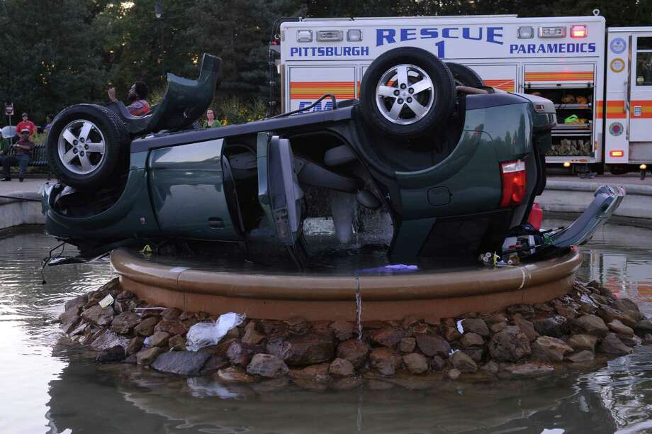 This Sept. 26, 2013, photo shows a car that flipped into a fountain just inside the entrance of Highland Park in Pittsburgh.  The driver is in stable condition after his SUV crashed, went airborne, flipped and came to rest upside down in a fountain. Photo: AP